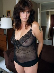 Curly mom in black transparent negligee