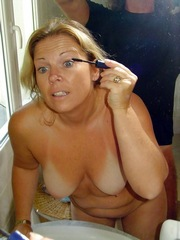 Beautiful naked blonde doing make-up on..